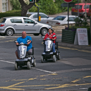People crossing the road on mobility scooters